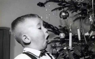 boy-blowing-christmas-tree-candle